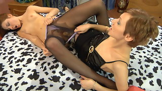 Lovely girl puts on black sheer-to-waist hose for role play with a strap-on
